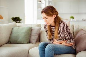 Eierstockentzündung: Frau krümmt sich vor Schmerzen
