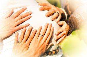 Hände wollen Babybauch berühren