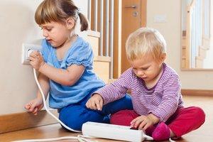 Kinder spielen mit einer Steckdose