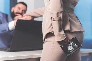 Arbeitnehmerin steht mit Ultraschallbild vor ihrem Chef
