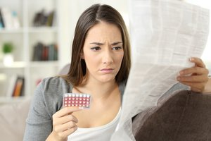 Antibiotika und Pille: Frau liest Beipackzettel