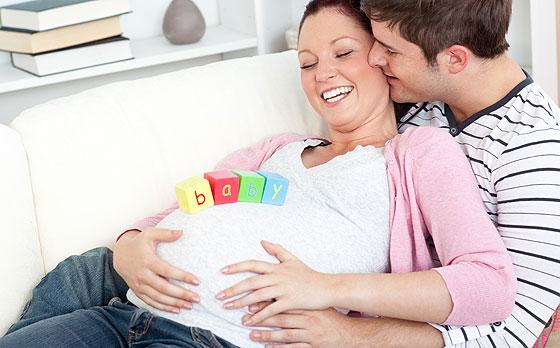 Schwangere liegt in den Armen ihres Partners