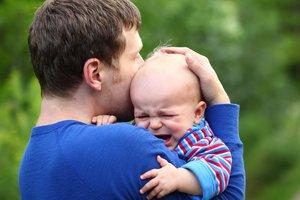 Vater tröstet Baby mit Bauchschmerzen