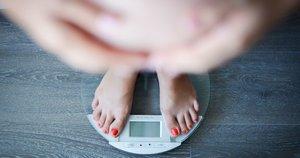 Körpergewicht und Kinderwunsch: Frau auf der Waage