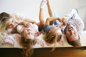 Das Bett ist der perfekte Spot für wunderschöne Familienfotos. Alle fühlen sich wohl und sind auf einer Ebene.