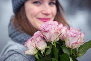 Freundliche Frau mit Rosenstrauß