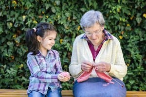 Seniorin bringt Mädchen das Stricken bei.