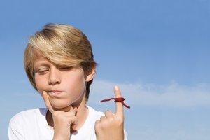 Rechts oder links? Junge mit Bindfaden am Finger.