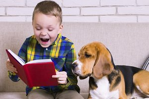 ein Junge liest einem Hund etwas vor