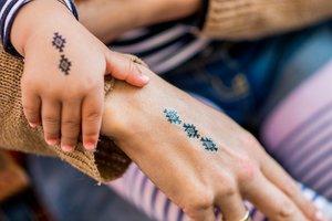 Kinderhand auf Mamas Hand, beide mit gleichem Abziehbild tätowiert